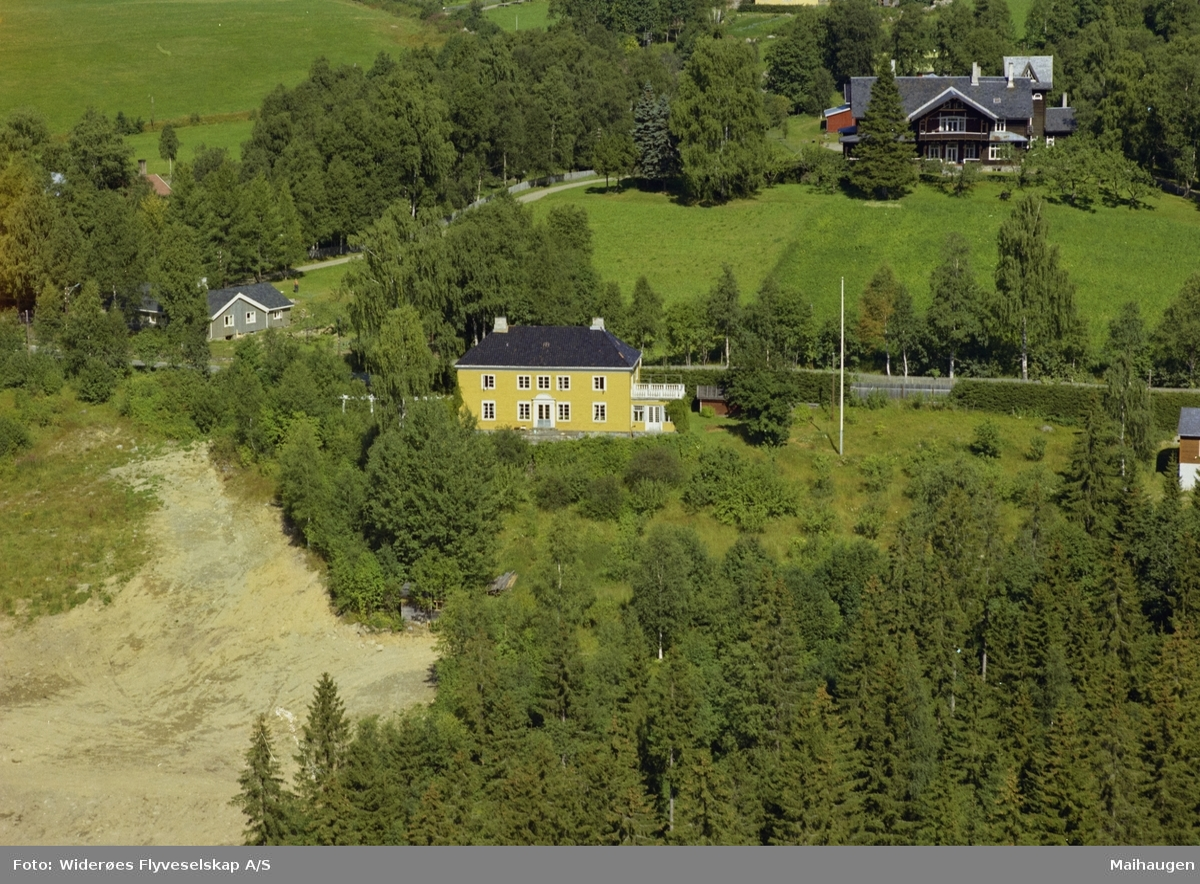 Stor gul villa bygd av fru Wiegaard, Granheim. Hage med busker. Granskog rundt. Kornhaug bak i bildet