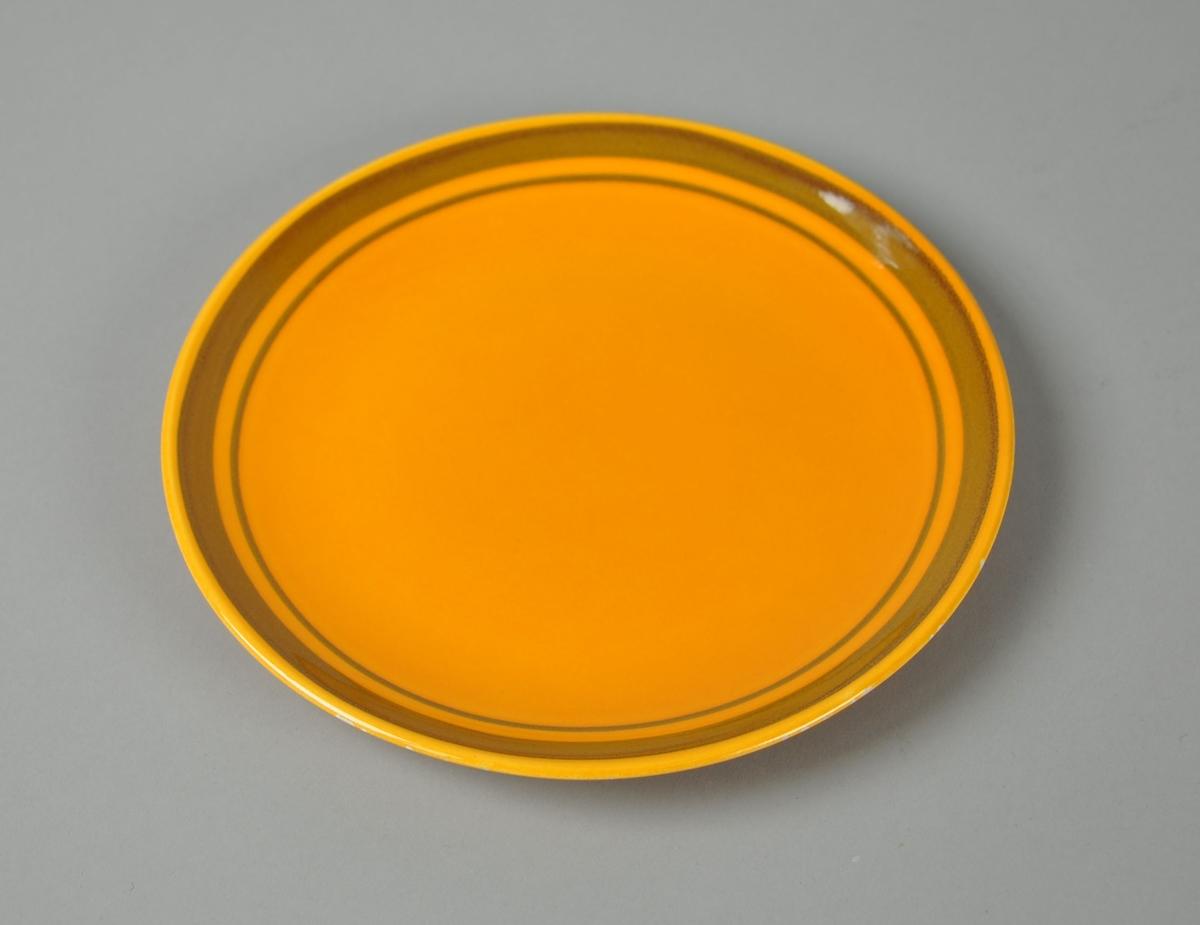 Oransje asjett av glassert keramikk. Rundt kanten av asjetten går det to brunfargede sirkler, en tykk og en tynn.