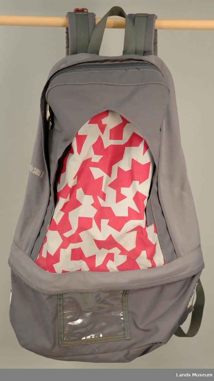 Grå sekk med krystallmønster i rosa og grått på fronten. Fløyte montert på.