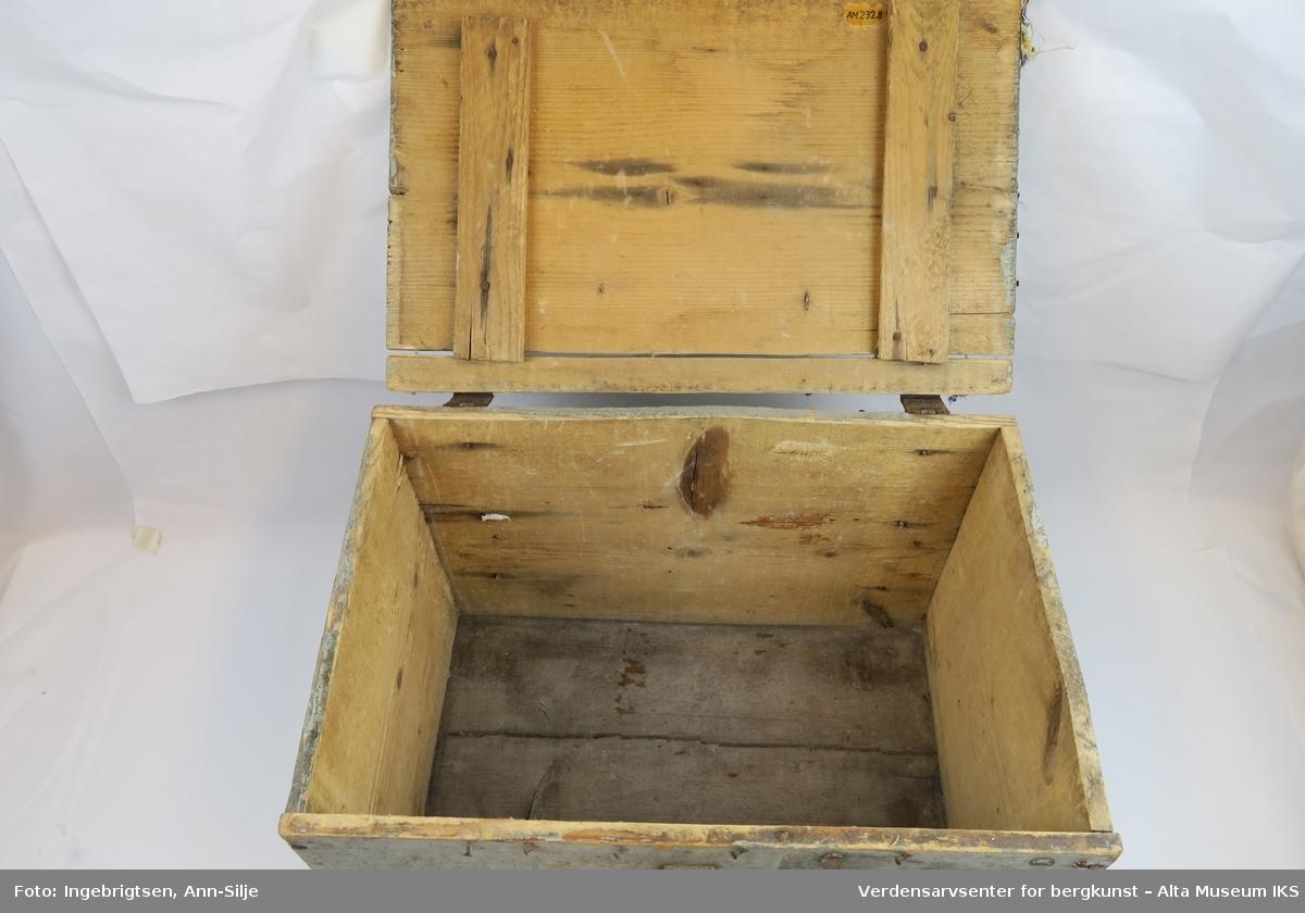 """Teknikk: Spikret sammen av 11 1/2"""" ulimte bord slik at skrinets høyde, bunn og lokk har samme dimensjon ( 11 1/2""""= 29,5 cm.) Form: Rektangulær kasse med hengsler, låsbeslag og håndtak av jern. En god del av malingen på kassen er flaket av."""