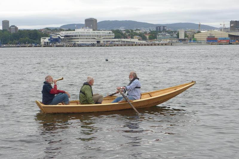 Tre menn ombord Holmsbuprammen, Oslo i bakgrunnen. (Foto/Photo)