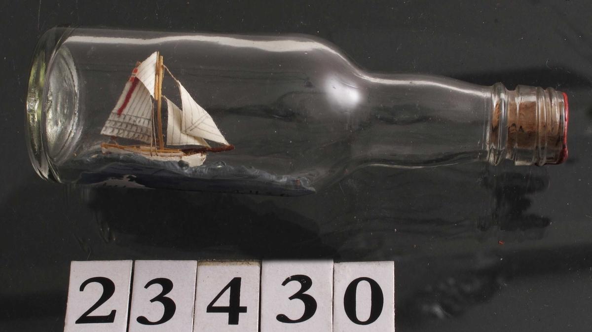 Mini flaskeskip: Losbåt.  Glass, klart. Kork med rød lakk. Hvitmalt miniatyrskute med rød bunn og rød stripe i seilet. Blå sjø.