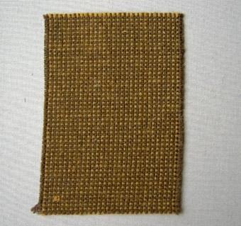 Vävprov, brunt möbeltyg i ull vävt i panamabindning med färgeffekt. Varp i två olika nyanser brunt 2-trådigt ullgarn; möbeltygsgarn. Två trådar löper tillsammans. Inslag i brunt 2-trådigt ullgarn; möbeltygsgarn.