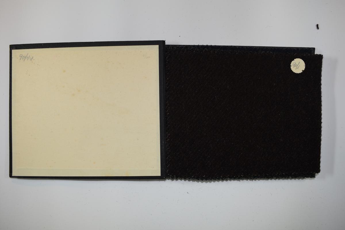 Prøvebok med 4 stoffprøver. Tykke ensfargede stoff. Bare fargen varierer mellom prøvene i boken. Stoffene ligger brettet dobbelt slik at vranga dekkes. Vranga viser tydelig veven, mens forsiden tilsløres av fibre. Stoffene er merket med en rund papirlapp, festet til stoffet med metallstift, hvor nummer er påført for hånd.   Stoff nr.: 90/1, 90/2, 90/3, 90/4.