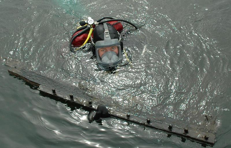 Dykker med båtdel i overflaten