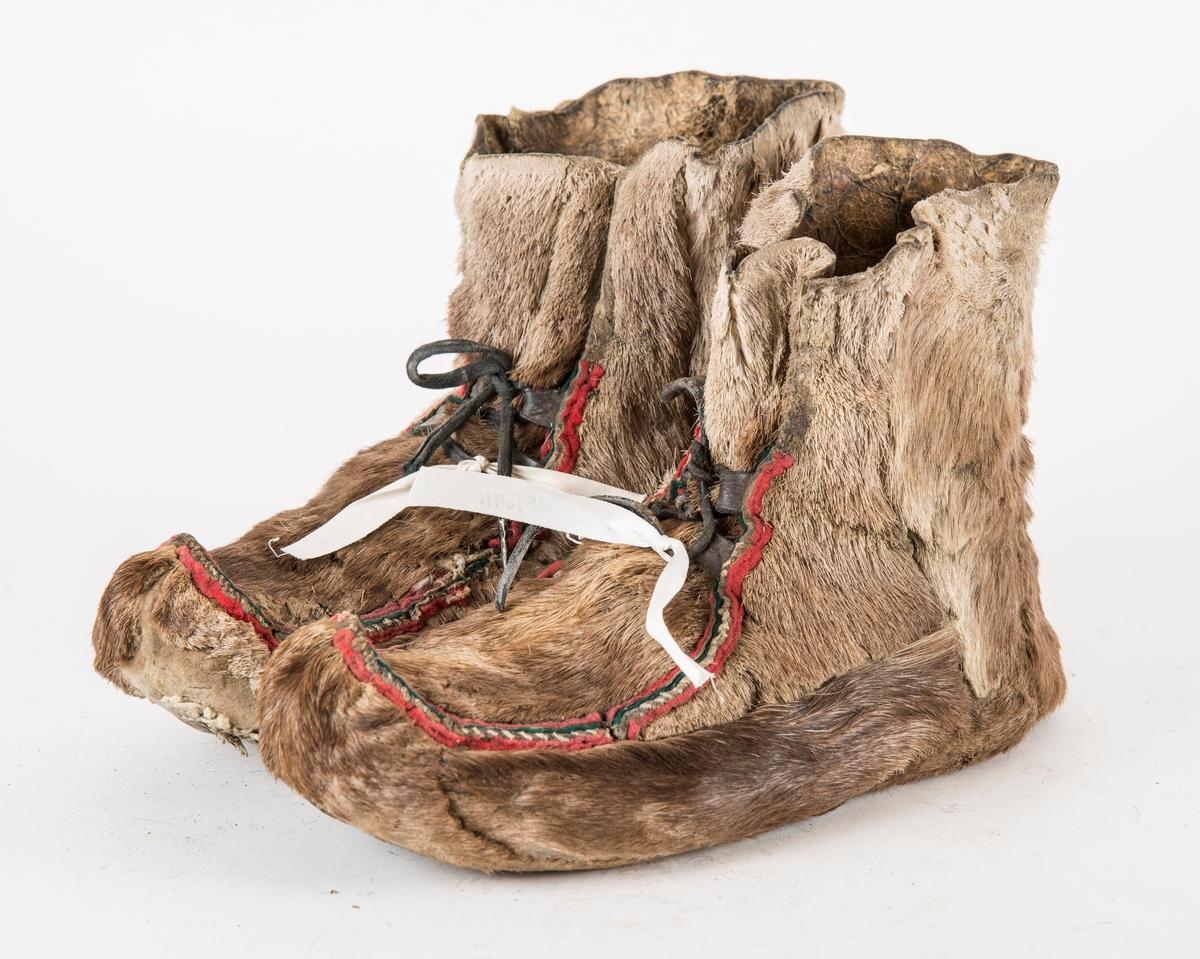 Sko, A og B, hudsko av reinskinn. Sauma av bektråd. Raud og grønn filtkant i saumen opp på foten. To par skinnhemper til snøringa, Lisser i lér.