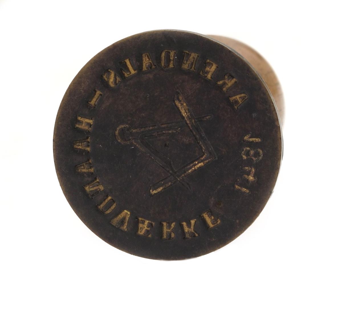 Signet, fra Arendals Haandværkf. stiftet 1847. Dreiet håndtak, bøk, polert. Signet messing, sirkelrundt,  inngravert tekst  som ovenfor langs kanten, passer og  vinkelmål i midten. Preget forgylt.