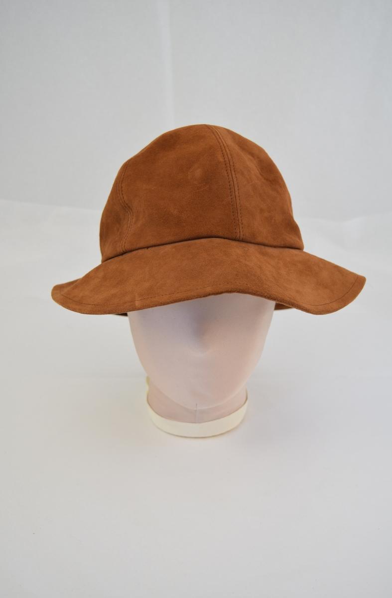 Hatt av semsket skinn.  Hatten er rund med brem, bremmen er noe smalere på hattens bakside. Hoveddelen består av seks trekantede stykker og bremmen består av et stykke. Foret med tynt hvitt stoff på innsiden.