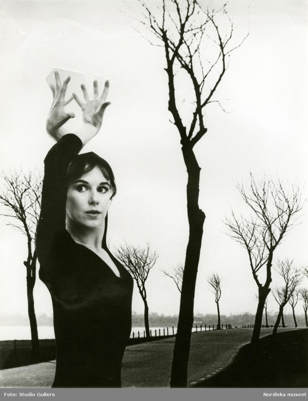 Kvinna poserar med uppsträckta armar framför en landskapsbild med väg och kala träd, troligen montage