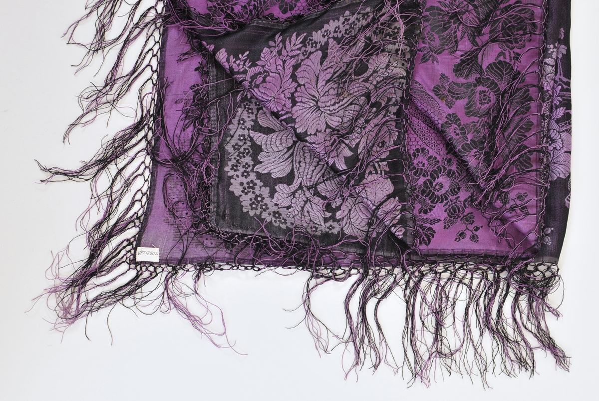 Silketørkle i damask i fiolett og svart. Påsydde frynser i same fargane. Falda (tråkla) på to sider og jarekant i to.