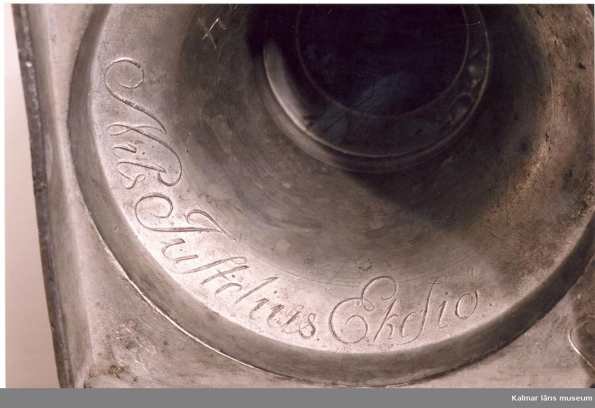 KLM 7084:1-2. Ljusstakar, ett par, av tenn. Äggformiga ljushållare, uppbäres av en refflad uppåt avsmalnande kolonn. Fotställning klockformig på fyrkantig platta nederst fyra kutformiga fötter. Stämplar, kontrollstämpel, mästarstämpel, NEJ ( Nils Eric Justelius), Eksjö, P4 (1845).