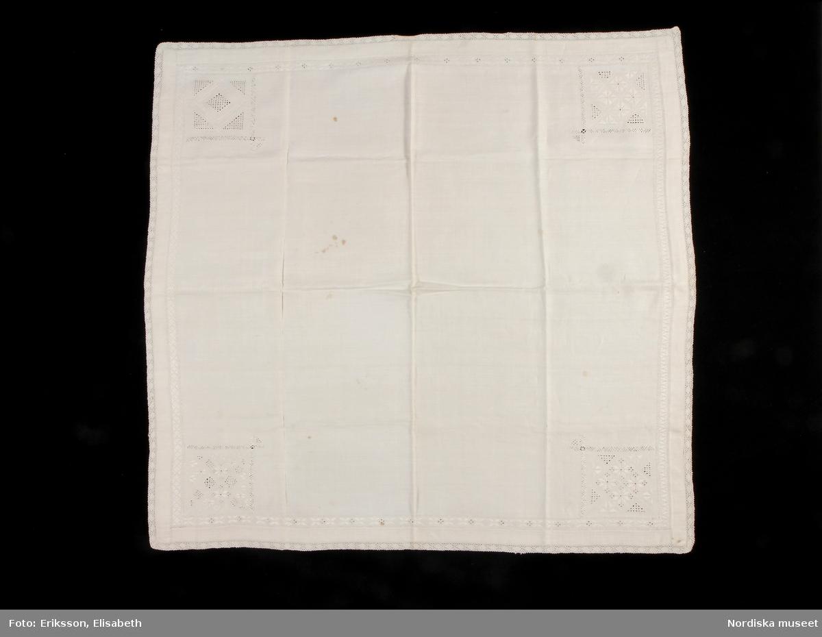 """Kvadratiskt kläde i handvävt  linne. Invikt fåll, 2,5 cm bred, 1,7 cm bred broderad bård i rätlinjig plattsöm med inslag av dubbel utdragssöm, i fållkant, enkel utdragssöm i kanterna. Kvadratiska hörnbroderier, ca 11 x 11 cm, i alla hörn. Broderierna består av rombiska, kvadratiska och rektangulära former i utskårssöm, rätlinjig plattsöm och stopphålssöm. Utdragssöm i kanterna. Broderierna utförda i vitt lingarn. Alla hörnmotiv är olika. Handknypplad uddspets, 1,5 cm bred spets utmed alla sidor. På baksidan av varje hörn finns en langetterad hank att fästa tygdekorationer, s.k. vippor i. Klädet är handsytt. Anm: Några fläckar.   Utdrag ur Svensson Sigfrid, (1935). Skånes Folkdräkter, en dräkthistorisk undersökning 1500 - 1900. Stockholm: Nordiska Museets Handlingar: 3, sid. 262 - 263: """"Härmed kan sammanställas Linnés uppgift från Göinge: 'Torrklädet' är et linne armkläde, wid kanterna genombåradt och sydt samt med spetsar kantadt och med wippor i hörnen utsiradt'. Dessa benämningar - 'näsduk', 'torrkläde' och 'armkläde' - förekomma i bouppteckningarna redan vid 1700-talet början och åsyfta tydligen då en duk, som burits på armen eller hållits i handen...Från Ö. Göinge omtalar Eva Vigstsröm, att till fästmögåvorna också hörde en 'kinnaklud' och enligt beskrivning var denna av fullkomligt samma utseende som armklädet. Om dess användning säges: 'Denna klut bands helt utbredd öfver brudens hår, då hon red eller åkte till kyrkan.' Samma bruk har förekommit i Ingelstad: 'Under resan till och från kyrkan hade bruden öfwer locken, liksom öfwer kluten, ett 'hyeklä', ett fyrkantigt tygstycke af linne med genombrutet arbete.'. Enligt Wistrand användes samma plagg även vid kyrkobesök och resor och Svanander omtalar hyeklädets användning till sorgdräkten, fig 242. Att armkläde och hyekläde förkomma samtidigt i bouppteckningarna torde bero på en senare differentiering. Ett och samma slags linneduk har kunnat användas som förningsduk, 'bokkläde' och 'gudmoraklut' (som bars av fadd"""
