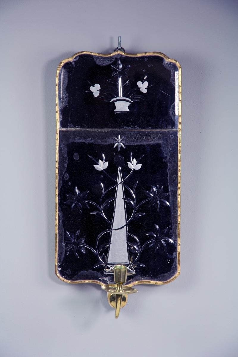 Spegellampett för ett ljus, av tvådelat glas, med förgylld blyinfattning. Rektangulär med mjukt rundade hörn och fasade kanter och från baksidan inslipad dekor. På övre glaset en blomsterkorg, på undre glaset en obelisk omslingrad av blomsterrankor. Ljushållare av mässing. Bakstycke av trä. Brännstämpel NS under krona för Nils Sundström samt Stockholms Hallstämpel 1770.