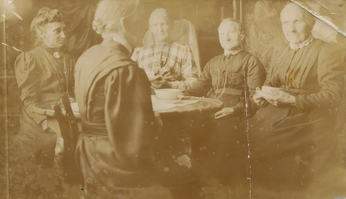 """Forsamling rundt bord, fotounderlag for """"Misjonsforeningen""""."""
