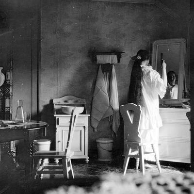 Kvinne grer segpå soveværelse, 1905