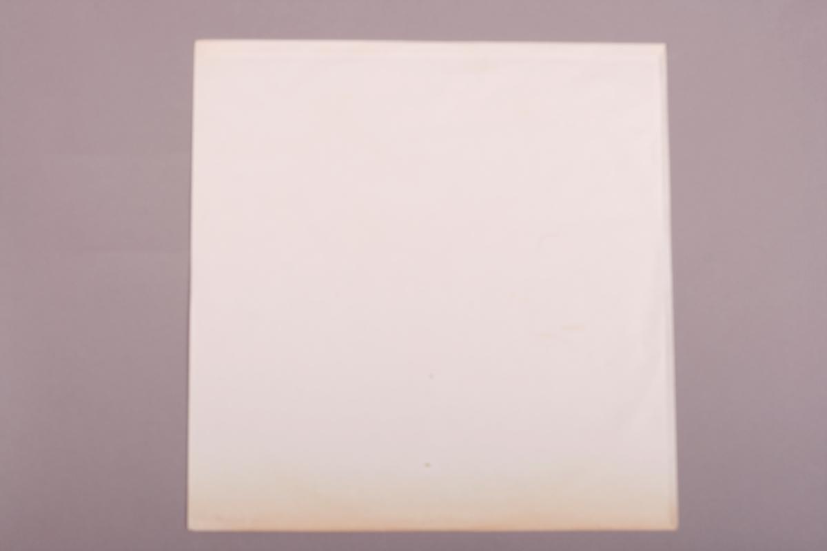 Grammofonplate i svart vinyl og plateomslag i papp. Omslaget er fortsatt innpakket i plastt, men skåret opp på høyre side. Plata ligger i en papirlomme.