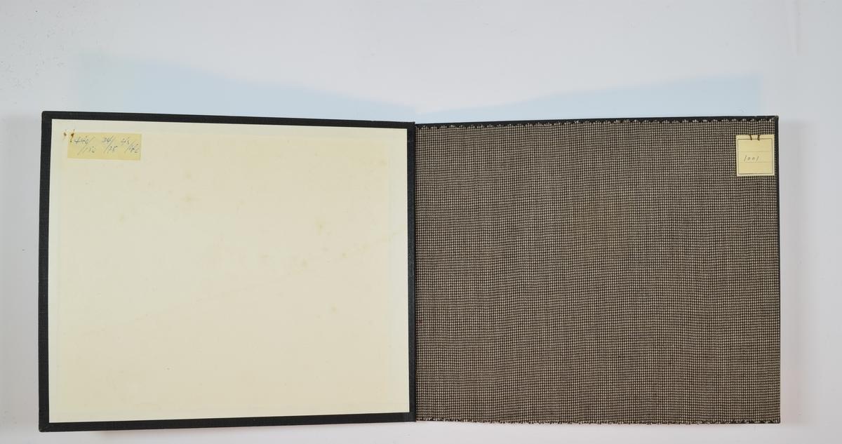 Prøvebok med 1 stoffprøve. Tynt stoff. Stoffet er ikke monokromt, men vevd av tråder i fargene brunt, sort og hvitt. Stoffet ligger brettet dobbelt i boken slik at vranga dekkes. Stoffet er merket med en firkantet papirlapp, festet til stoffet med metallstifter, hvor nummer er påført for hånd.   Stoff nr.: 1001