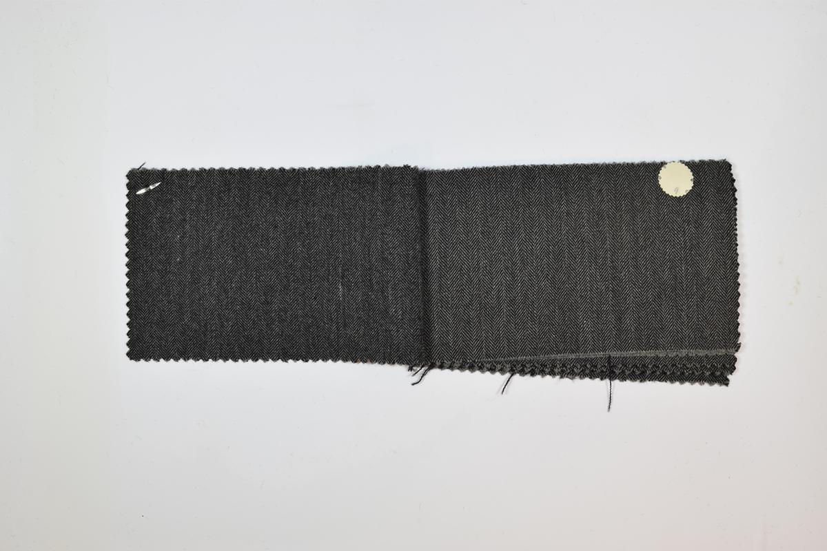 Sammenstiftede stoffprøver, 7 ulike stoff. Relativt tynne stoff med fiskebensmønster blant annet. Mønsteret på de tre første stoffene er likt, men fargen varierer. På de resterende stoffene er mønsteret ulikt, men fargen den samme. Stoffprøvene er klippet med sikksakk-saks langs alle kanter. Alle stoffer er merket med en rund papirlapp festet med metallstifter hvor nummer er påskrevet for hånd. Det er rimelig å anta at alle stoffene har kvalitetsnummer 1766 grunnet plasseringen av tallene på lappene, samt likheten mellom stoffene.   Stoff nr. 1766/8, 1766/9, 1766/10, 1766/11, 1766/12, 1766/13, 1766/14.