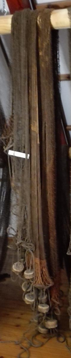 Brunt bomullsgarn med runde korkar og med blylodd som søkke. Maskestørrelse: 5,7 cm (frå hjørne til hjørne).