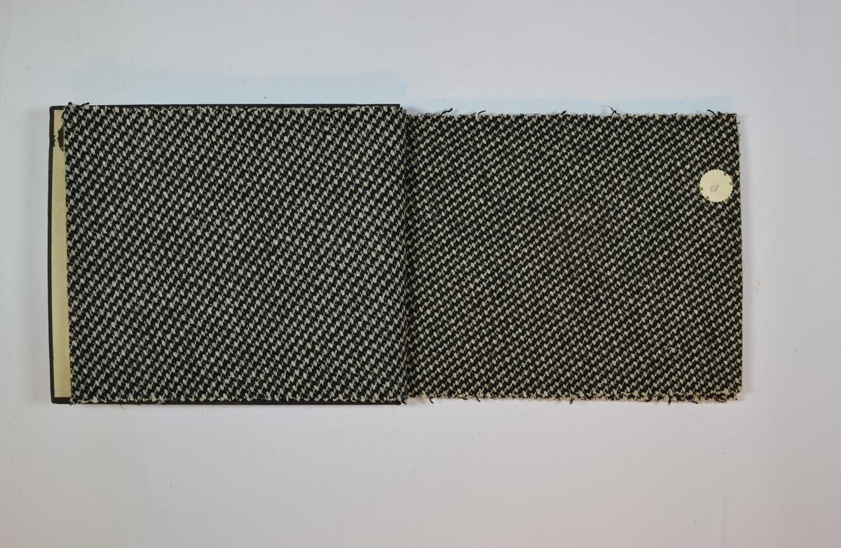 Rektangulær prøvebok med 5 stoffprøver. Middels tykke stoff med skrå striper. Kyperbinding/diagonalvevd. Fargen på stoffene varierer. Stoffene ligger brettet dobbelt i boken slik at vranga dekkes. Stoffene er merket med en rund papirlapp, festet til stoffet med metallstifter, hvor nummer er påført for hånd. Alle numrene er krysset over med rød fargeblyant. Påskriften på innsiden av forsideomslaget indikerer at alle stoffene har kvalitetsnummer 1850.   Stoff nr.: 1850/80, 1850/81, 1850/82, 1850/83, 1850/84.