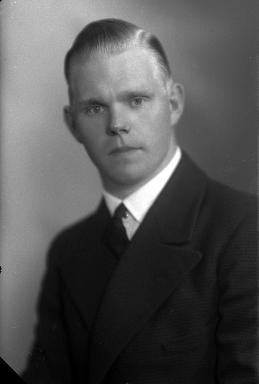 Ateljébild på en man i kavaj. Enligt Walter Olsons journal är bilden beställd av herr Gust. Nilsson.