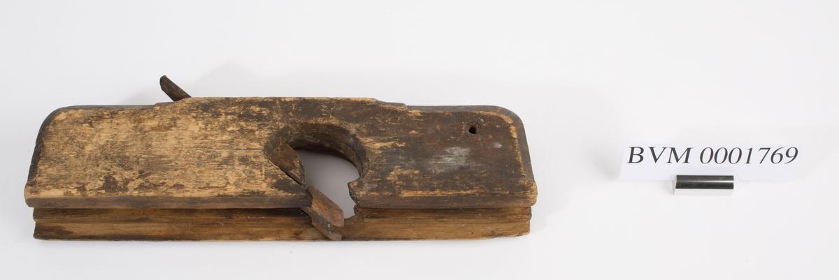 Fjærhøvel i tre med kile og høveljern. Styrekant på venstre side. Gjennomgående hull i front på høvelstokken.