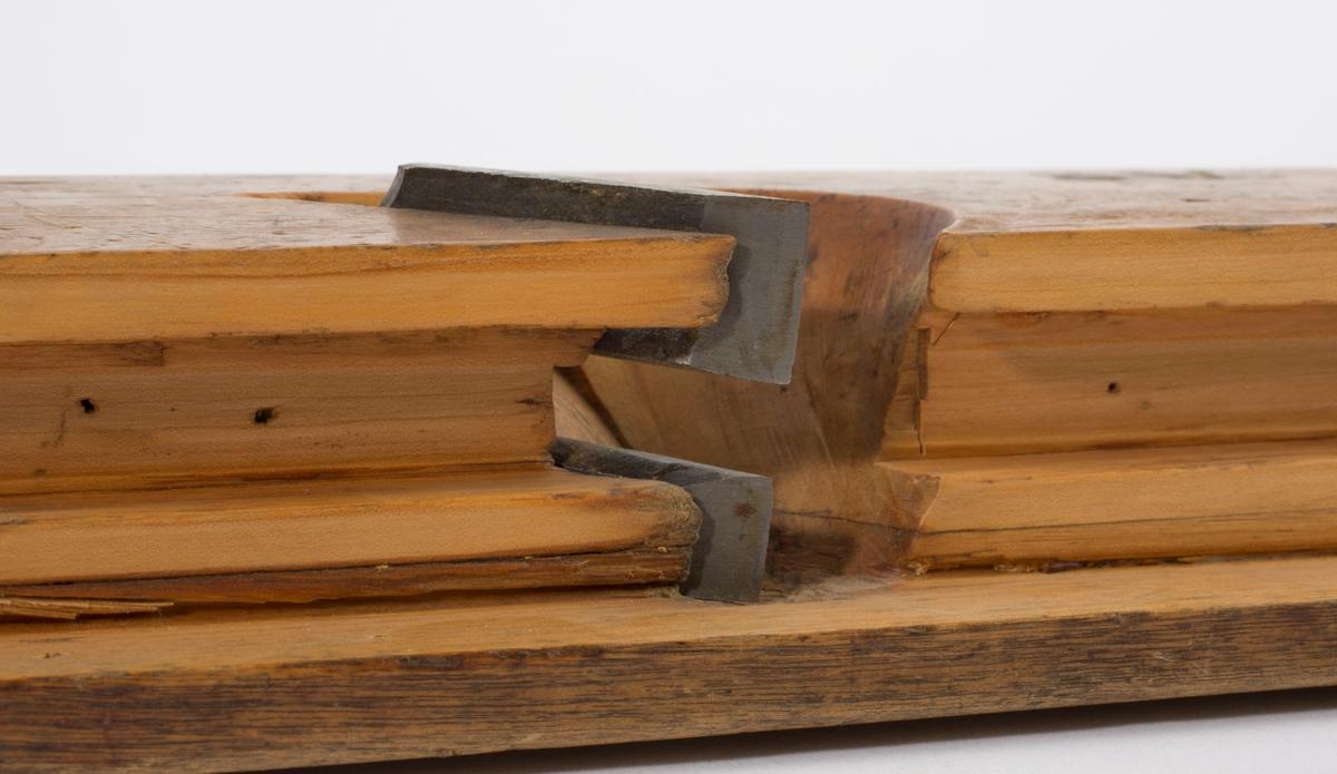 """Fjærhøvel i tre med kile og høveljern. Styrekant på venstre langside. På høyre langside er bokstavene """"SV"""" brent inn. Gjennomgående hull i front på høvelstokken."""