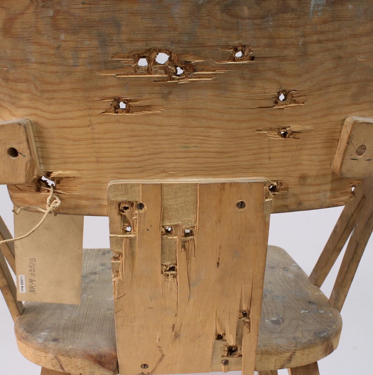 Stol i tre med flere skuddhull gjennom ryggstøet. Under setet er det slått inn en firetoms spiker.