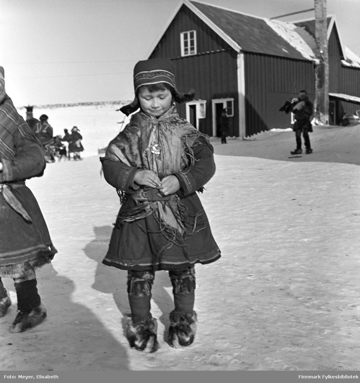 Berit Nilsdatter Logje på plassen utenfor Kautokeino Skoleinternat. Berit har på seg samisk kofte, sjal, sølje, lue, skinnbukser og skaller med skalleband. Det er stor aktivitet på plassen, barn i lek og voksne i arbeid. Sannsynligvis fotografert ved påsketider 1940.