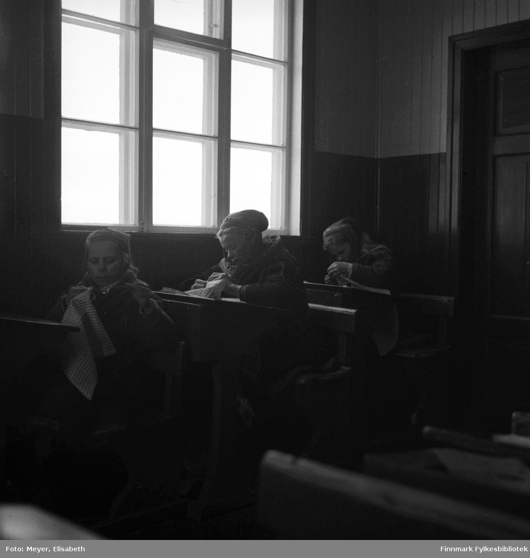 Fotografert i en skolestue - elever sitter ved skolepulter og broderer. Foran i bildet sitter Brita Isaksdotter Triumf. Bak henne sitter Marit Ravdna Nilsdatter Gaup. Jenta bakerst har vi ikke fått navn på.