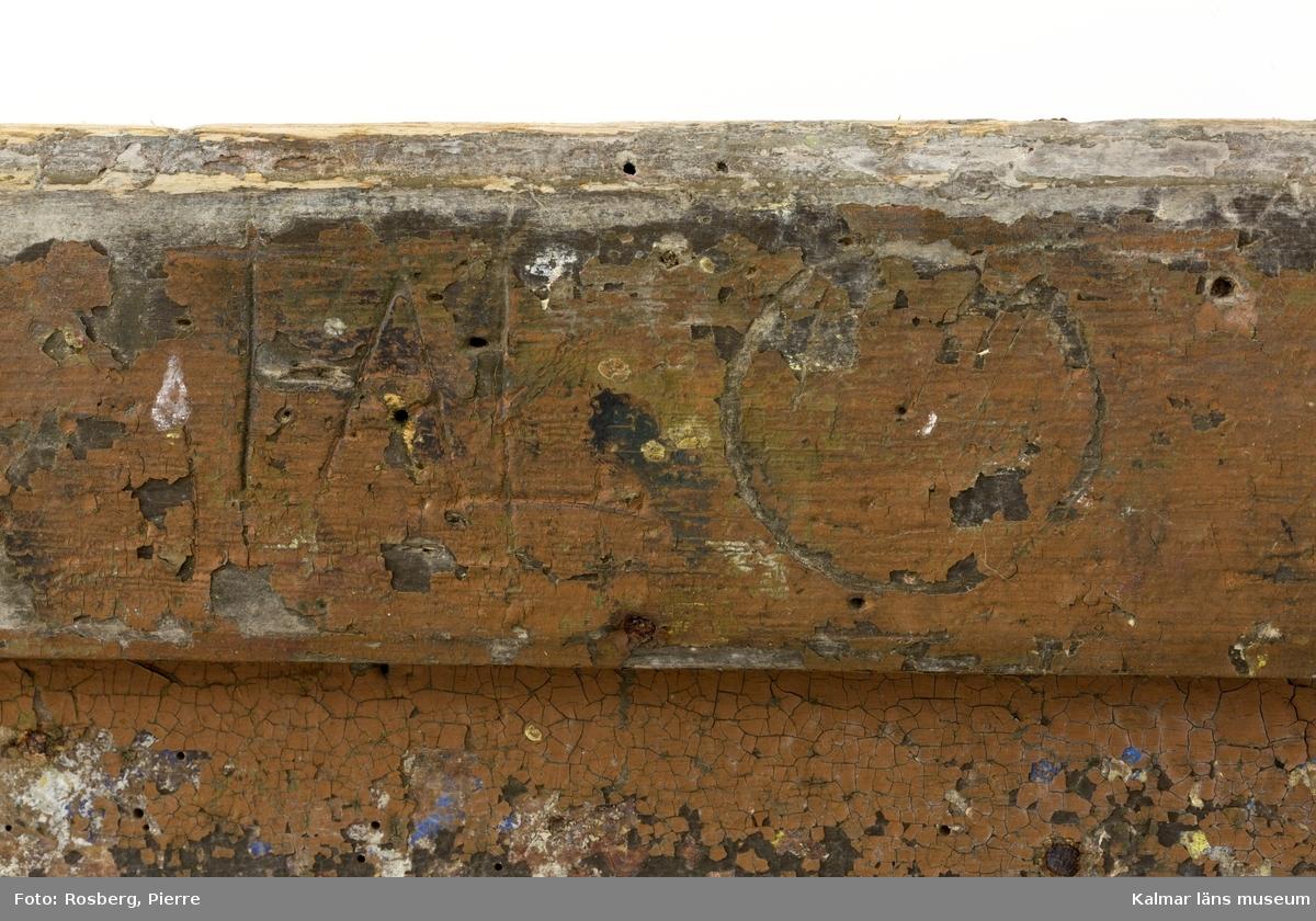 KLM 10947:1. Tryckpress för tapeter. Tryckpress med fyra ben, de två bakre utgör även bakstycket som har en fastmonterad järnstång för fäste till pressdelen. På kortsidorna sitter slåar halvvägs upp mellan fram- och bakbenen. På långsidorna fram och bak sitter slåar från ena sidan till den andra. Mellan frambenen finns en monterad järnstång som utgör andra fästet för handtaget till pressdelen. Mellan det högra fram- och bakbenet har en grov trädel suttit, likaså mellan det vänstra fram- och bakbenet. Trädelarna har fungerat som extra stöd och gjort tryckpressen mer stabil. Överst på bordet ligger ett flertal filttyger samt grövre säckväv varav några är fastspikade i bordet. Upptill på höger bakre ben syns en inristad ring med stiliserad blomma inuti. På baksidan inristat text på två ställen: TAL.