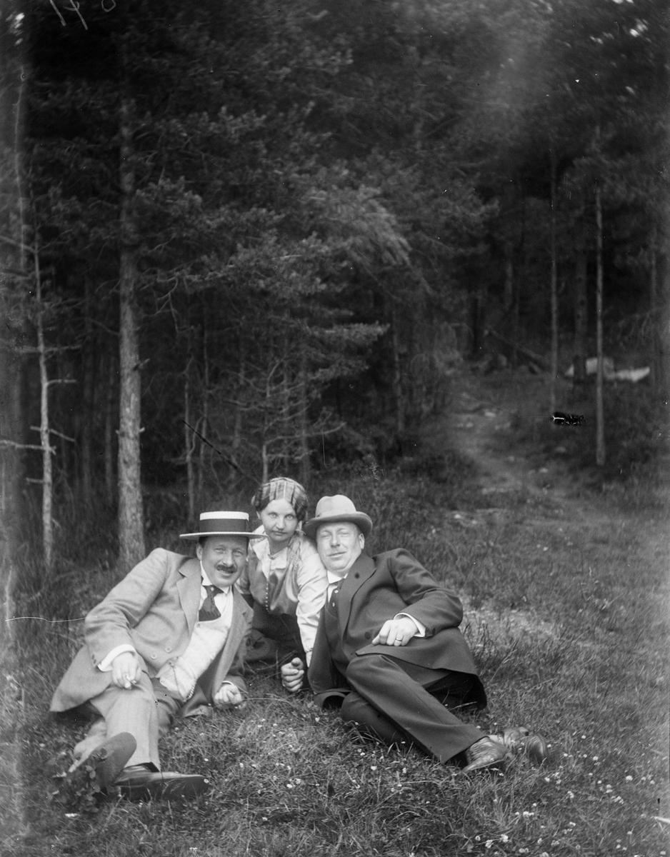 Tvä män och en kvinna vid skog, Uppland