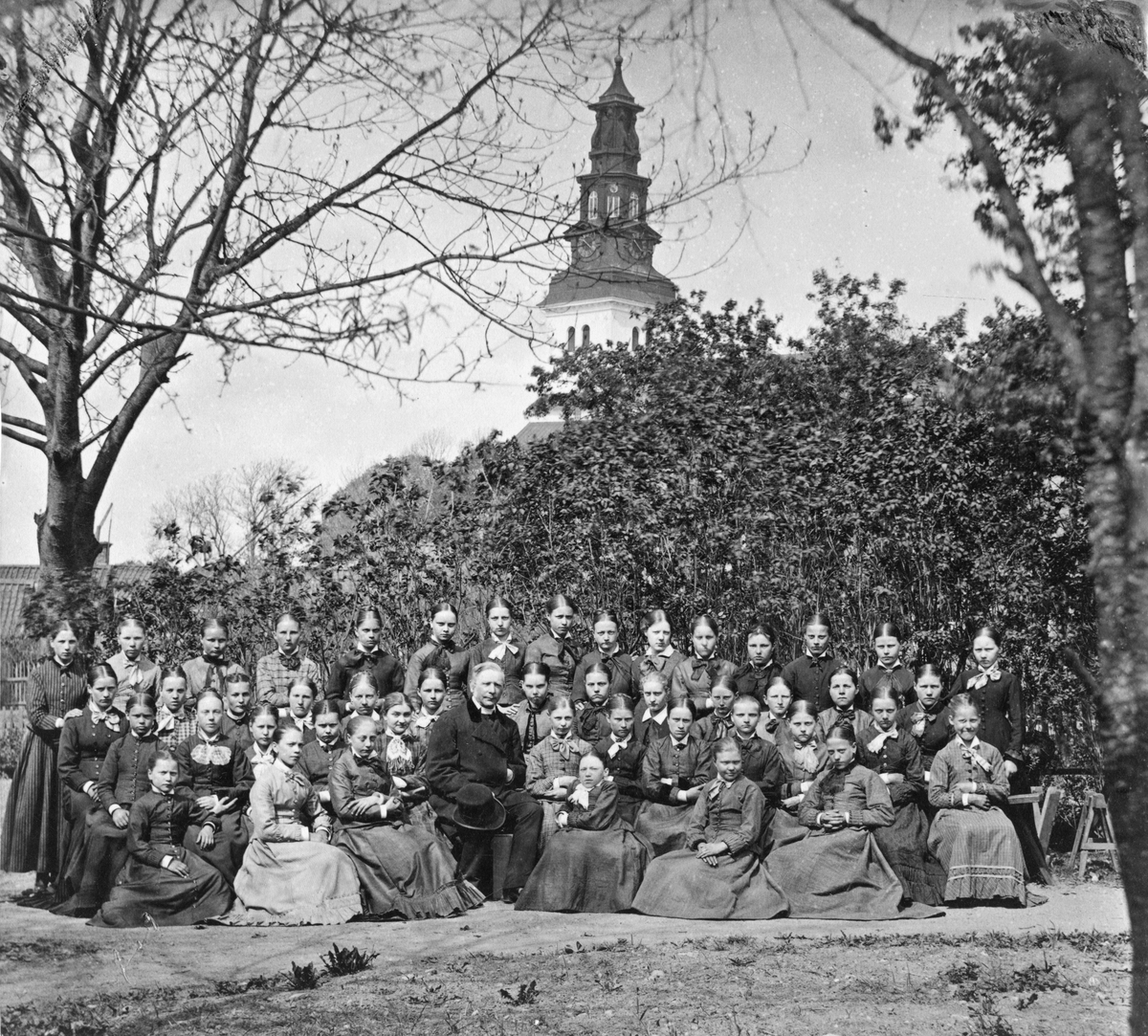 Konfirmander (flickor) 1879 med prästen Arhusiander. Se bild 2 för namnförteckning.