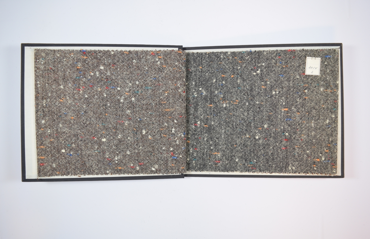 Rektangulær prøvebok med tre stoffprøver og harde permer. Permene er laget av hard kartong og er trukket med sort tynn tekstil. Boken inneholder middels tykke, melerte stoff med tilsynelatende tilfeldigplasserte prikker i friske farger. Toskaftbinding med hvit tråd i den ene retningen og sort og/eller brun i den andre retningen. Mønsteret for alle stoffene er likt, men fargen og fargekombinasjonene er ulike. Stoffene er merket med en firkantet papirlapp, festet til stoffet med metallstifter, hvor nummer er påført for hånd.   Stoff nr.: 2014/1, 2014/2, 2014/3.