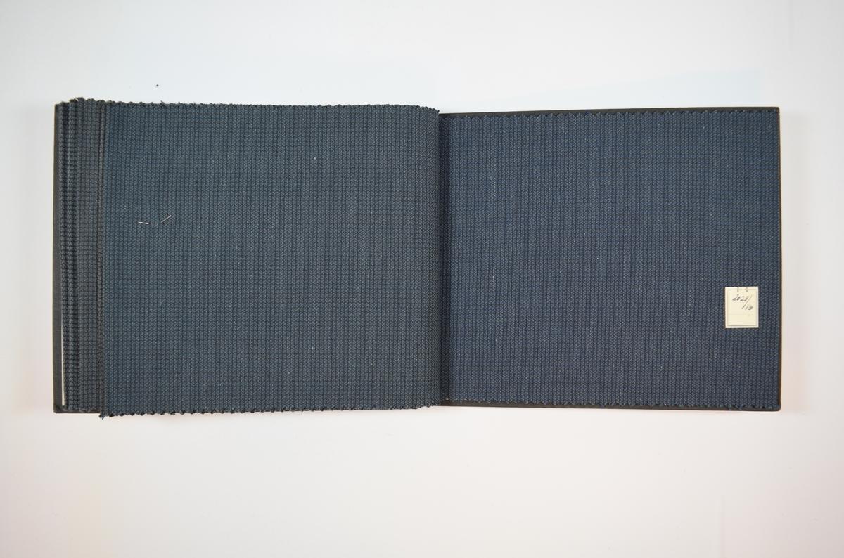 Rektangulær prøvebok med seks stoffprøver og harde permer. Permene er laget av hard kartong og er trukket med sort tynn tekstil. Boken inneholder middels tykke, flerfargede stoff med smårutemønster. Kyperbinding/diagonalvevd. Alle stoffene har omtrent det samme mønsteret, men fargene varierer. Stoffene er merket med en firkantet papirlapp, festet til stoffet med metallstifter, hvor nummer er påført for hånd.   Stoff nr.: 2028/11, 2028/12, 2028/13, 2028/14, 2028/15, 2028/16.