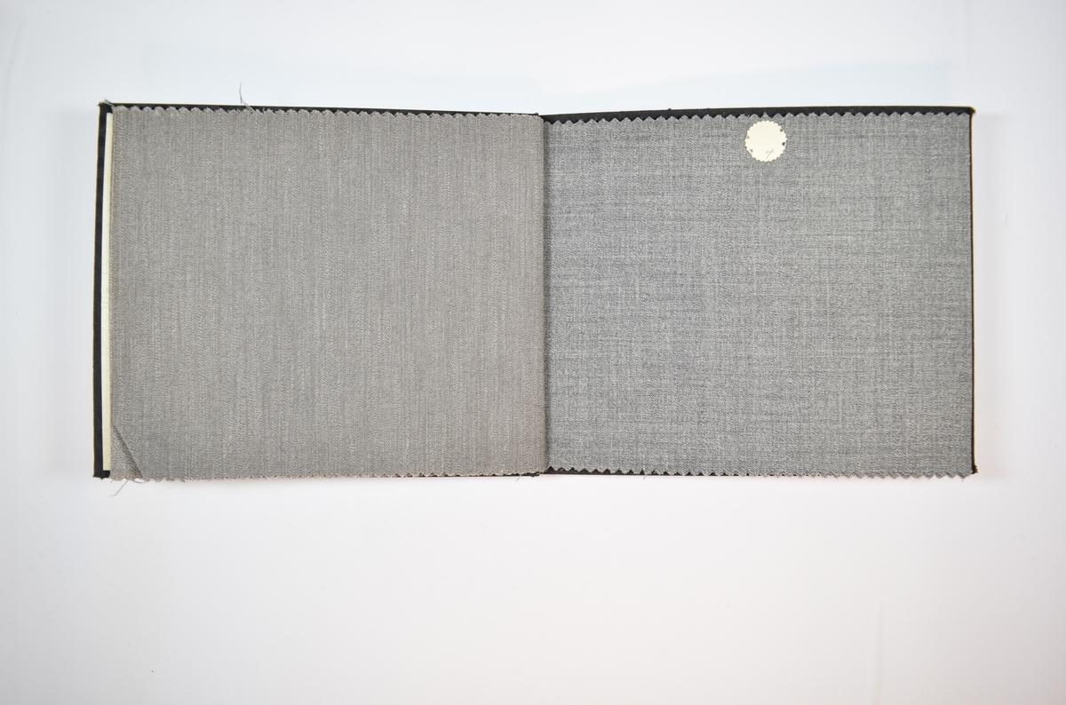 Rektangulær prøvebok med seks stoffprøver og harde permer. Permene er laget av hard kartong og er trukket med sort tynn tekstil. Boken inneholder tynne, men tette, melerte stoff. Toskaftsbinding på flere av stoffene, men ikke på alle. Det er trolig små variasjoner i vevmønsteret boken skal vise. Alle stoffene ligger brettet dobbelt i boken slik at vranga dekkes. Stoffene er merket med en rund papirlapp, festet til stoffet med metallstifter, hvor nummer er påført for hånd. Innskriften på innsiden av forsideomslaget viser at alle stoffene i boken har kvalitetsnummer 3300.   Stoff nr.: 3300/1, 3300/2, 3300/3, 3300/4, 3300/5, 3300/6.