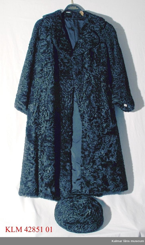 KLM 42851:1 Mössa, för kvinna, pälsskinn. Rund mössa av svart smålockigt pälsskinn, eventuellt persian. Hör ihop med päls KLM 42851:2.