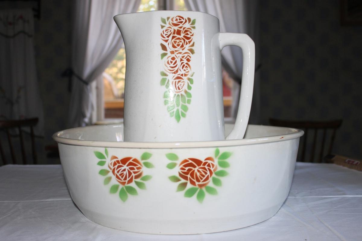 Handkanna i vitt porslin. Stiliserad, tryckt dekor med röströda rosor och gröna blad.