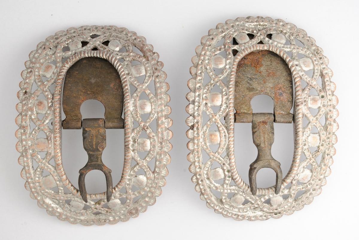 Skospenne, A og B, støypt i messing i gjennombrutt mønster. På framsida tinn eller nysylv. Spenna har oval form og er konveks. Stolpe, tann og kalv er i smidd jern.