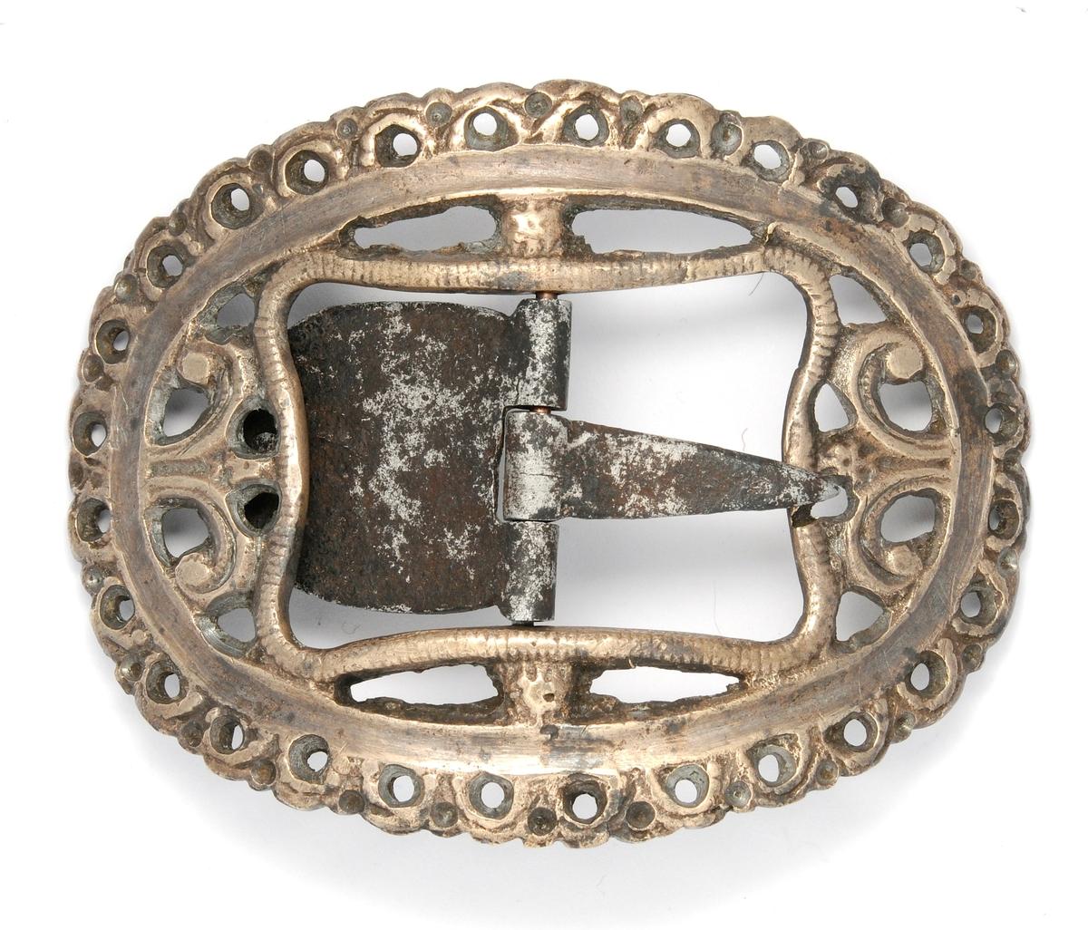 Spenne i messing, støypt med gjennombrote mønster.Tann, stolpe og kalv i smidd jern. Spenna er oval og konveks. Stolpe, tann og kalv i smidd jern. Pedant til VFF 02382.