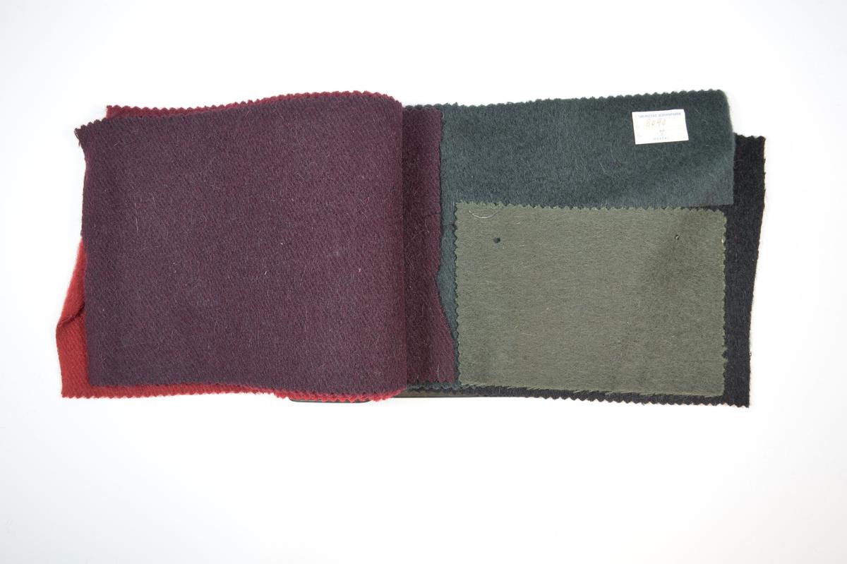 Prøvehefte med 6 prøver. Middels tykke ensfargede ullstoff i ulike farger. Vevmønsteret er synlig på stoffets vrangside (kyperbinding/diagonalvevd), mens rettsiden har et valket utseende. Stoffene ligger/har ligget brettet dobbelt i heftet. Stoffene er merket med en firkantet papirlapp klistret til stoffet, hvor nummer er håndskrevet i et trykket skjema. Heftet har stiv bakplate dekket av sort opak plast, samme type plate finnes på forsiden og dekker ca. 5 cm av forsiden der heftet er stiftet. En lapp i en plastlomme på innsiden av bakplaten gir informasjon om stoffet, blant annet materialene.  Stoff nr.: 8090/1, 8090/2, 8090/3, 8090/4, 8090/5, samt et umerket stoff som ligger løst i boken, kanskje 8090/6?