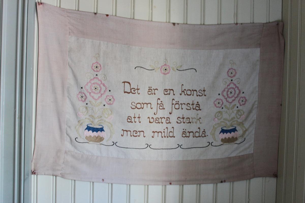 Väggbonad i tyg med broderat motiv och text. På en naturfärgad botten är broderat två blömkrukor med stiliserade blommor omgivande en text. Broderi med stjälkstygn, korsstygn, plattsöm och langettstygn i färgerna blått, brunt, grönt och rosa
