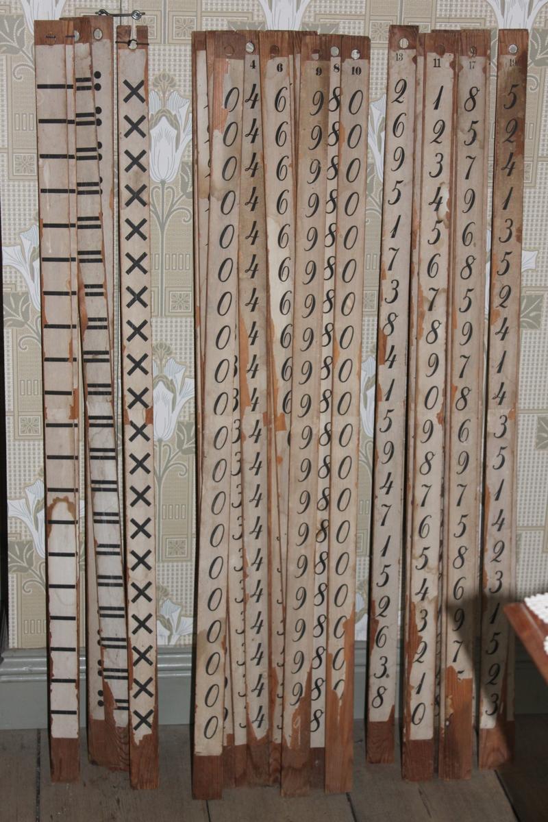 Räknestav i trä med påklistrad pappersremsa. Denna stav har tecknet för division längs hela stickan. Stickan placeras på svarta tavlan mellan stickor med siffror.