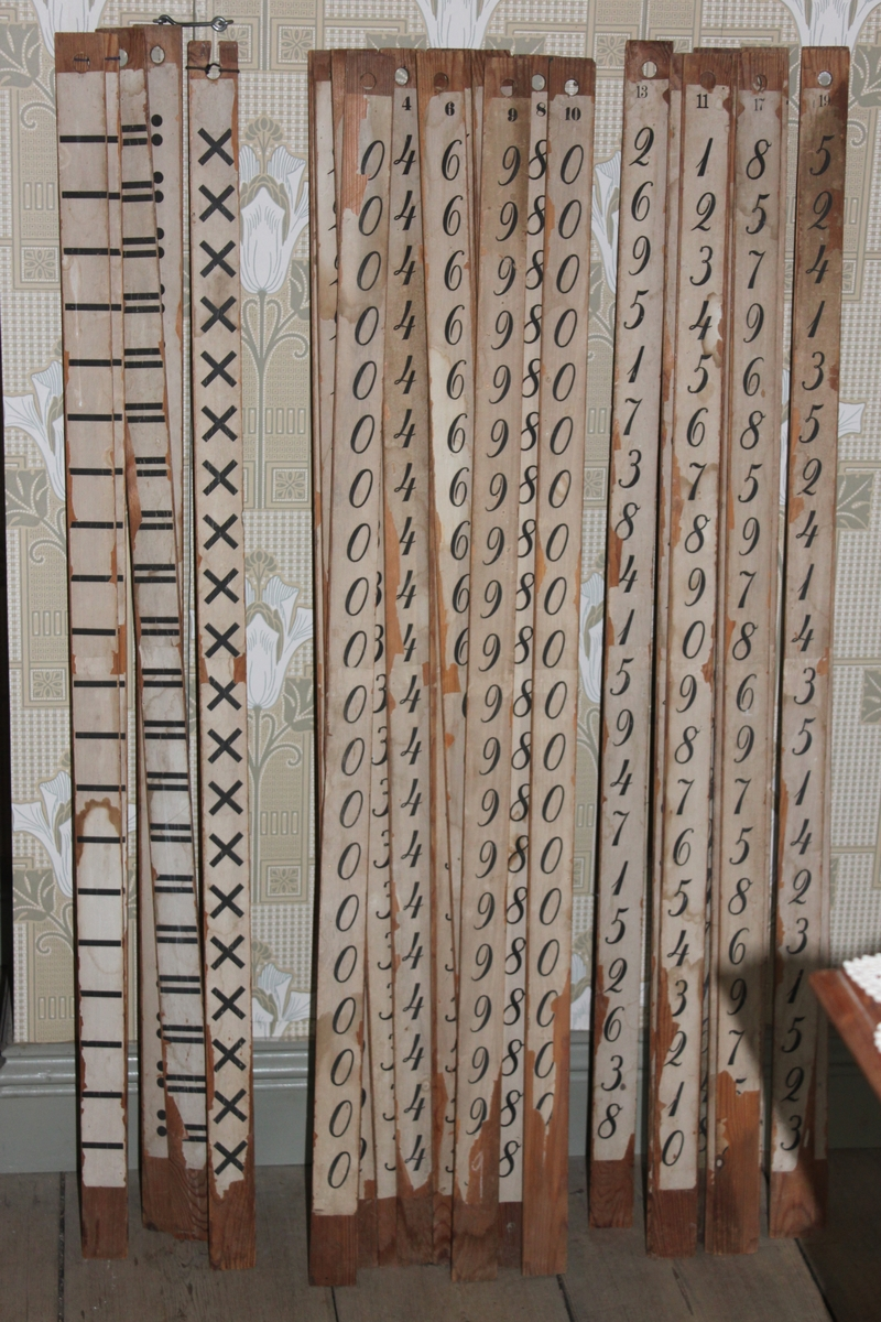 Räknestav i trä med påklistrad pappersremsa. Denna stav har tecknet för multiplikation längs hela staven.