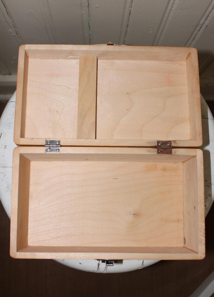 Förbandslåda från Räddningskåren. Tillverkad i trä med stängning, gångjärn och handtag i metall. Insidan av locket har en löstagbar smal träskiva där de tillhörande broschyrerna sätts fast.