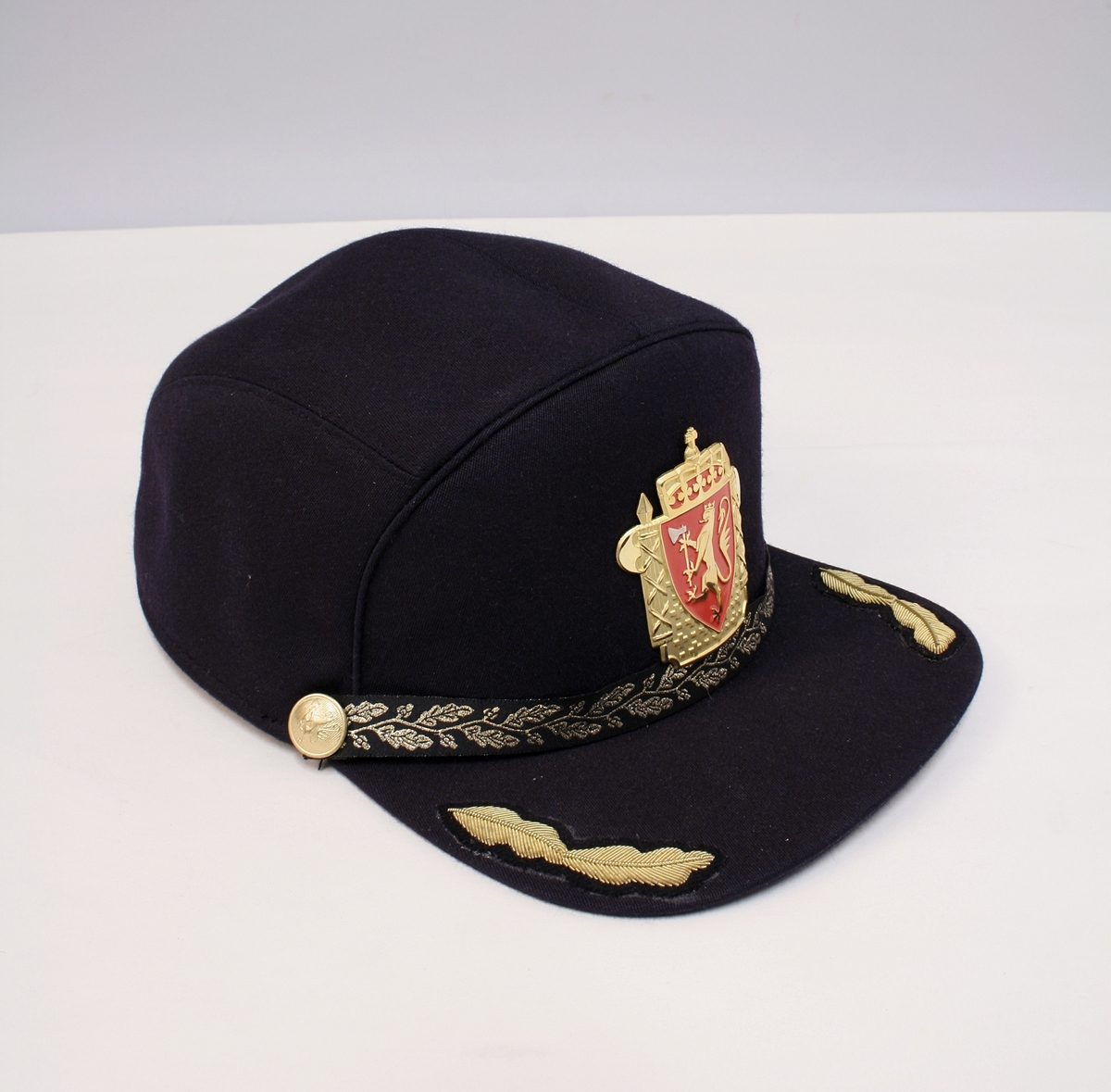 Sort uniformslue, tjenesteantrekk II - grunnform. Luemerke 1995 i metall, ekeløvsbånd, samt delt ekeløvsdistinksjon på skjermen, reglementert for f.o.m  politiførstebetjent t.o.m politiadjunktant.