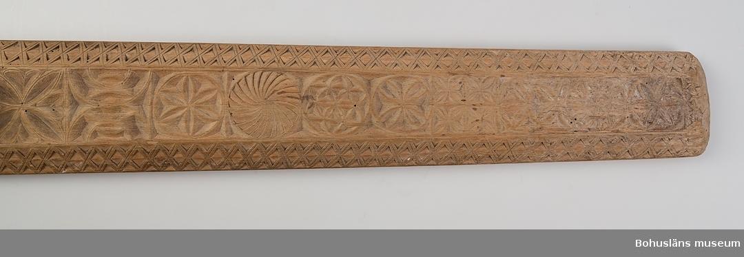 """Platt, rektangulärt redskap med handtag inskjutet i ett spår. Det är något avsmalnande framtill och har avfasade kanter. Ovansidan har ett band på mitten med karvsnittsdekor i form av fyrpass med inskrivna hjärtan, rosetter, virvelhjul samt annan geometrisk dekor. På de avfasade kanterna löper ett band med skuren rombdekor i uddsnitt. Runt handtaget löper följande text; """"Denna Sigud(?) hörer mig ma viga till år 1814. IPS MID (oläslig text) Den 4 mars 1814"""". Handtaget kan vara sekundärt. Sliten framtill, har mörknat undertill på grund av användning. Kavelrullen att linda tyget runt saknas. Skadedjursangrepp.  Litt.; Nylén, Anna-Maja, Hemslöjd, Håkan Ohlssons förlag, Lund, 1978, s. 359-363. Fredlund, Jane, Stora boken om livet förr, ICA-förlaget, Västerås, 1981, s. 40-49, 170-177. Sörensen, Steinar, Mangletreet, Glatteredskap og festegave, Glomdalsmuseets småskrifter nr. 3, Engers Boktryckeri A/S, Otta.  Ur handskrivna katalogen 1957-1958: Kavelbräde. dat.1814 Mangelbräde. L. 78 Br.12 Trä med karvsnittsmönster och text. Föremålet helt. Enstaka maskhål.  Lappkatalog: 72"""