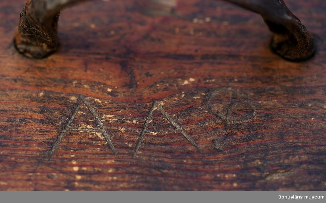 """Oval med löstagbart lock. På vardera """"kortsida"""" är ett urtag för """"knäpperna""""/ståndarna. Locket har ett böjt handtag mittpå. Svepet är fastsytt med kedjestygn. Söm av vidjor. Botten är fastsatt med tappar. Målad med mörkgrön färg som har mörknat på locket. Litt.; Granlund, John, Träkärl i svepteknik, Nordiska museets handlingar 12, Stockholm, 1940. Är nästan likadan som UM70.38.26 förutom att den är betsad och svepet är lagt åt motsatt håll.  Ur lappkatalogen: Smörtina, trä med lock. Tinan a) 15 x 11 x 24 cm; avlång, grönmålad. Locket b) 16 x 32 x 1 cm. Handtag på locket. Tinan söm av vidjor. Svepteknik. Anm. Har troligen aldrig innehållit smör.  Ang. D. Lundberg, se Svenskt Konstnärslexikon del III.  Personuppgifter, se UM70.38.1."""