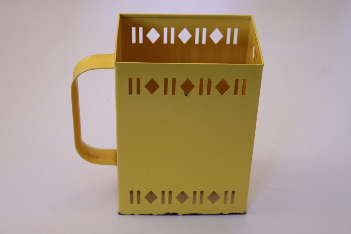 Hållare för mjölkkartong i gul plåt med handtag på ena sidan. Plåten har genombrutna mönset i en bård upptill och nedtill.