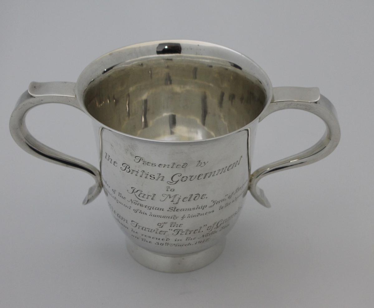 Redningspokal gitt til DS JERN ved Capt. Mjelde for redningen av mannskapet på PETREL av Grimsby i 1917. Sølvpokal med to hanker på lav stett med gravert dedikasjon.